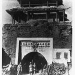Communist soldiers walking below Kuomintang slogans on one of the city gates which survived the siege of Jinzhou, 1948.