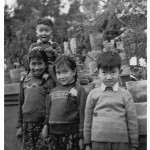 With Xiao-hong (left), Xiao-hei (behind), and Jin-ming (right), at the annual Chengdu flower show, 1958. Soon after this photograph was taken famine struck.  My father was constantly away in the countryside, so for several years there were no family photographs.