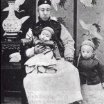 On her death-bed in 1908, Cixi made her two-year-old great-nephew, Puyi (standing), the next emperor, and his father, Zaifeng (seated holding Puyi's brother), the Regent.